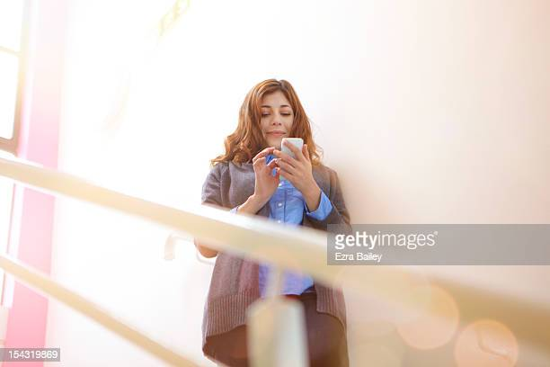 Woman checking her phone on the stairs