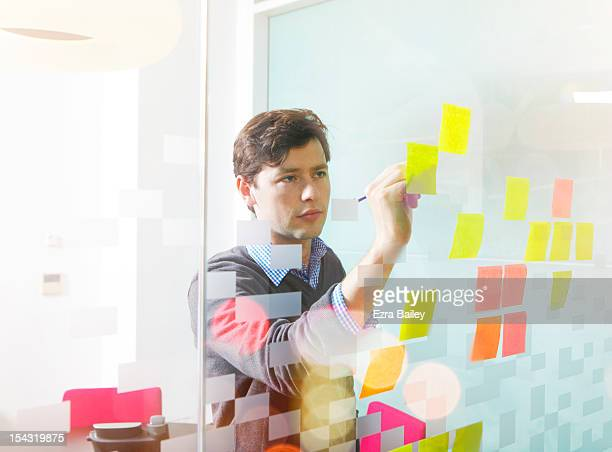 Businessman writing ideas on a sticky note.