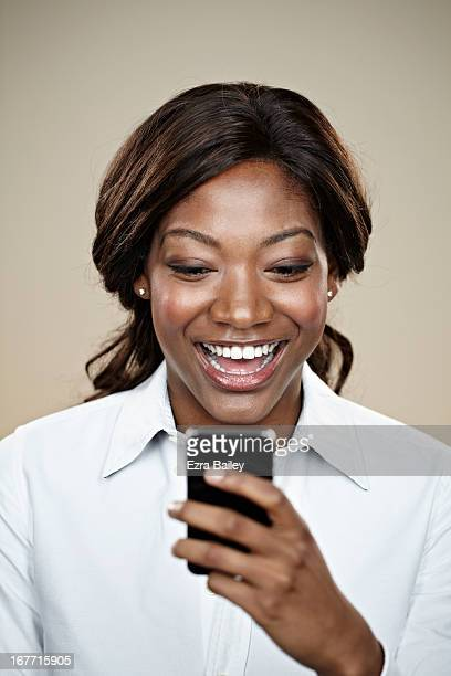 Female office worker smiling at her mobile phone.