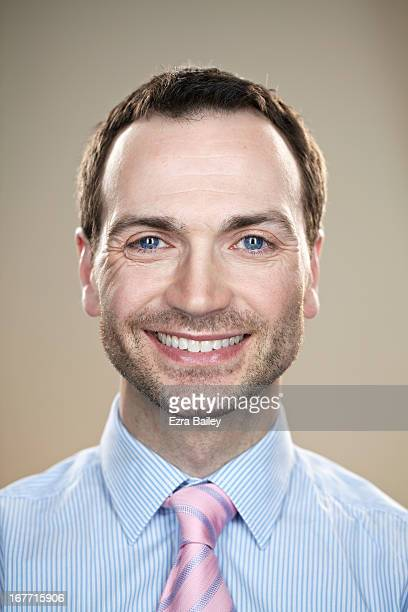 Male office worker smiling to camera.