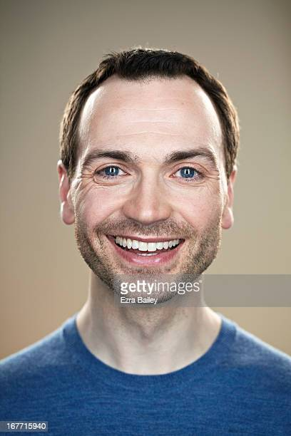 portrait of a man smiling into camera. - beige background stock pictures, royalty-free photos & images