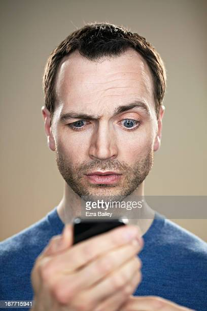 portrait of a man looking at his phone. - 眉を上げる ストックフォトと画像
