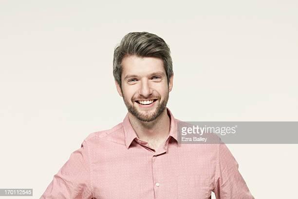 Man in a pink shirt smiling.