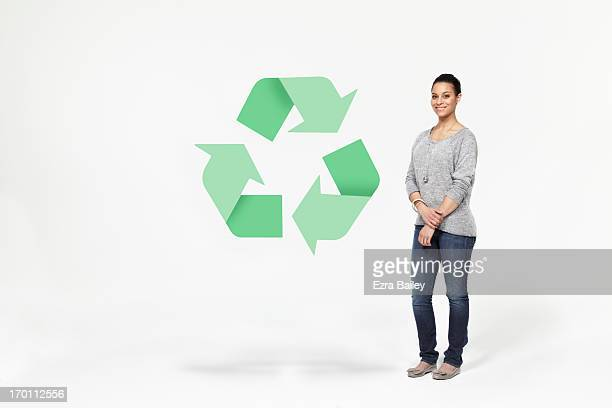 Woman standing next to recycling icon.