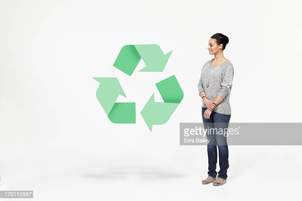 Woman looking at a recycling icon.