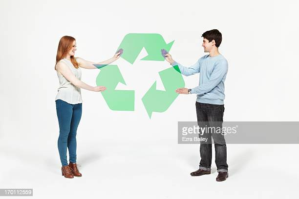Man and woman completing a recycling icon