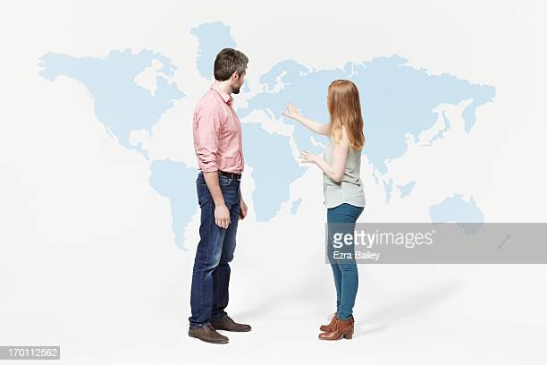 Man and woman discussing a world map.