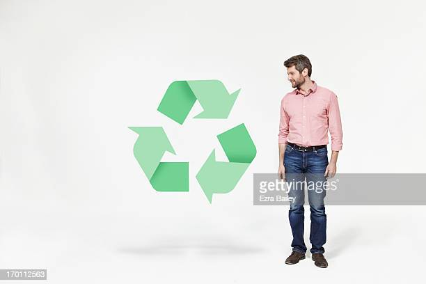 Man looking at recycling icon.