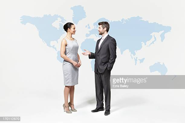 business people chatting in front of world map. - abbigliamento elegante foto e immagini stock