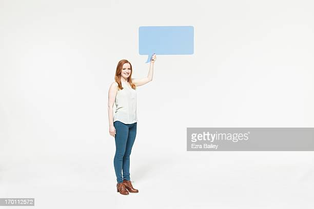 Woman holding speech bubble and smiling.