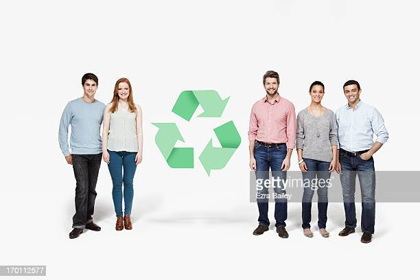 Group of people standing with recycling icon.