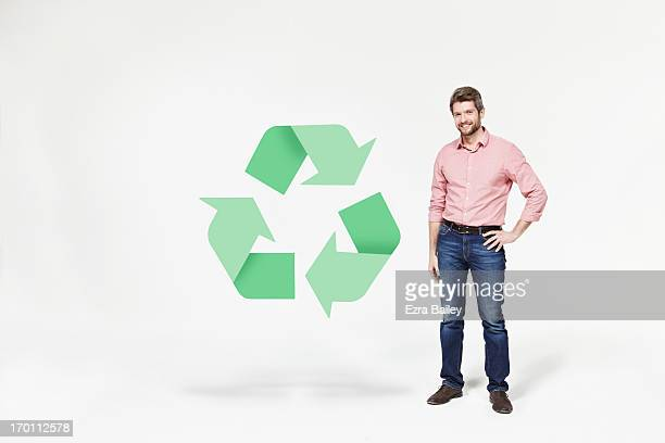Man smiling next to recycling icon.