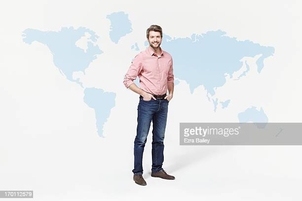 man in casual clothes standing with world map. - mains dans les poches photos et images de collection