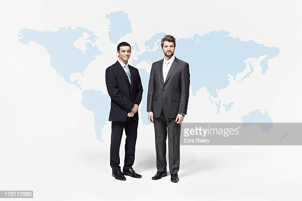 Businessmen standing in front of world map