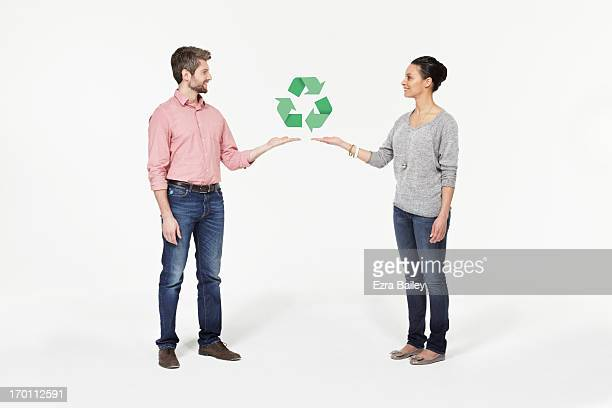 Man and woman with recycling icon.