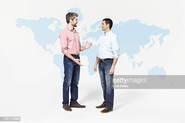 Two men chatting in front of world map.
