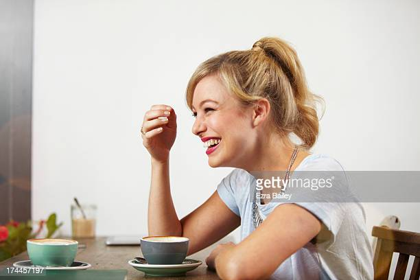 woman laughing in a coffee shop - ponytail stock pictures, royalty-free photos & images