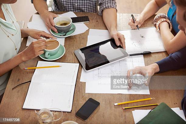 Colleagues working on a tablet in a coffee shop.