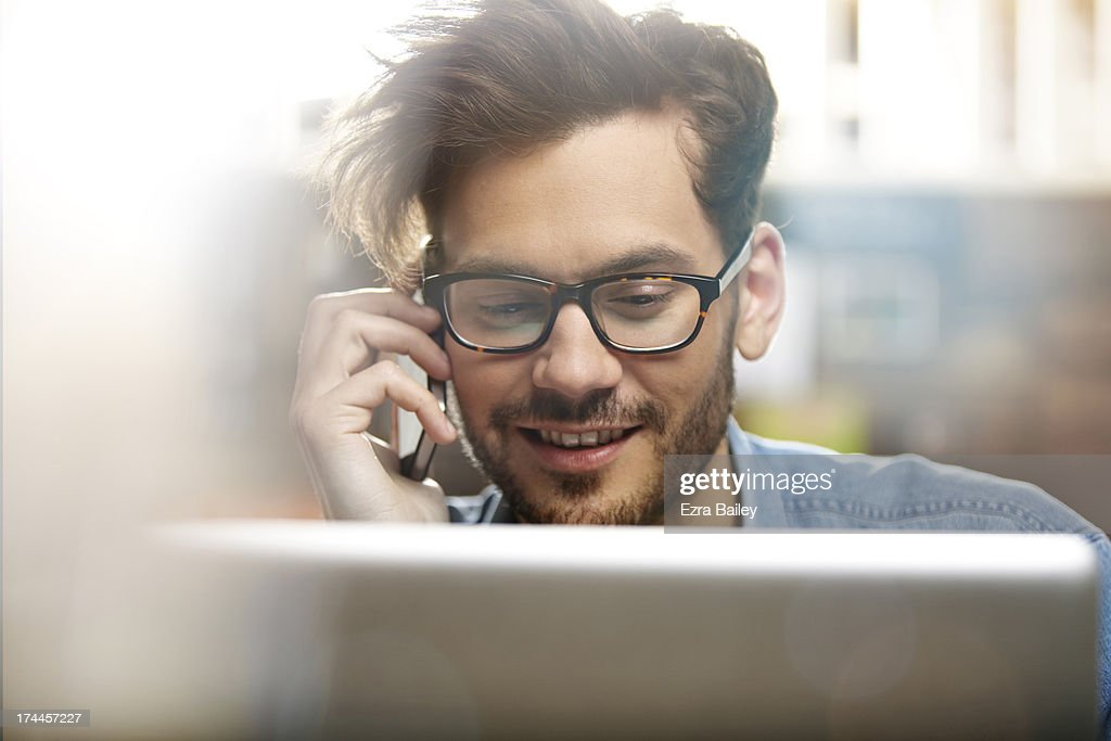 Man on the phone and using laptop : Stock Photo