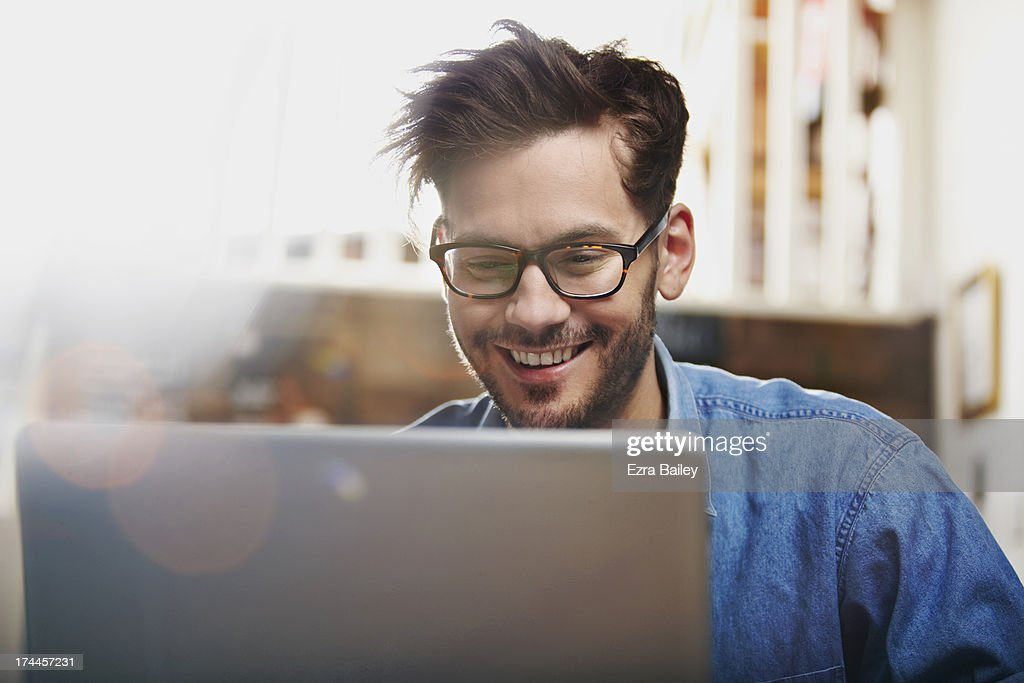 Man working on a laptop in a coffee shop : Stock Photo
