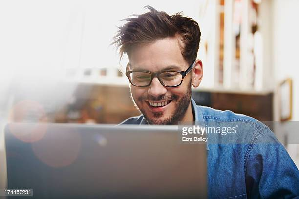 man working on a laptop in a coffee shop - surfing the net stock pictures, royalty-free photos & images