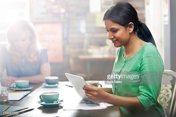 Woman working on a tablet in a coffee shop.
