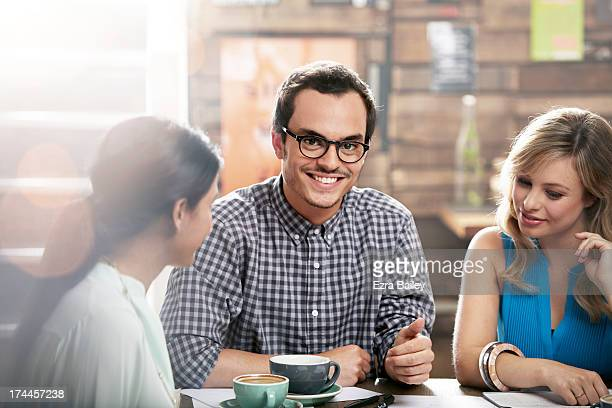 Man smiling in a coffee shop with friends.