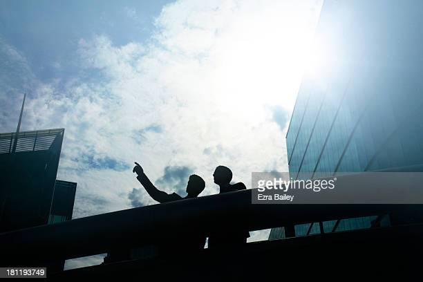 Two businessmen looking out over city skyline,