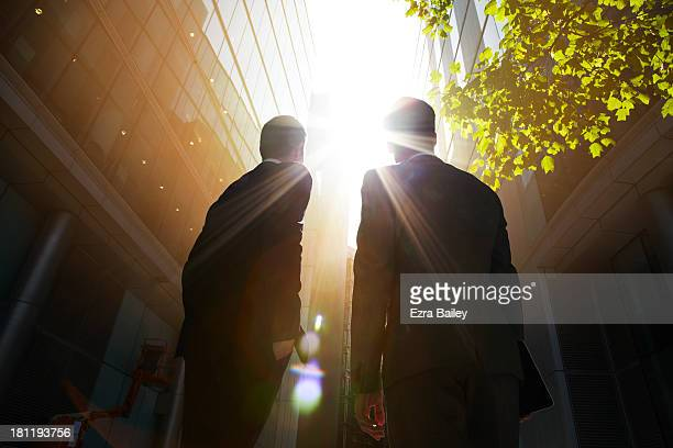 two businessmen looking up into the sun. - wachstum stock-fotos und bilder