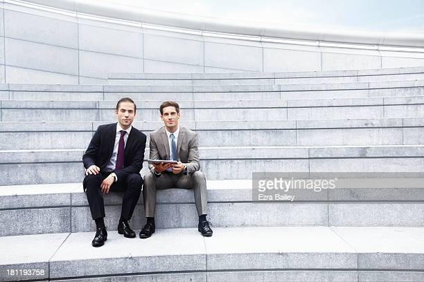 portrait of 2 businessmen outside holding a tablet - side by side stock pictures, royalty-free photos & images