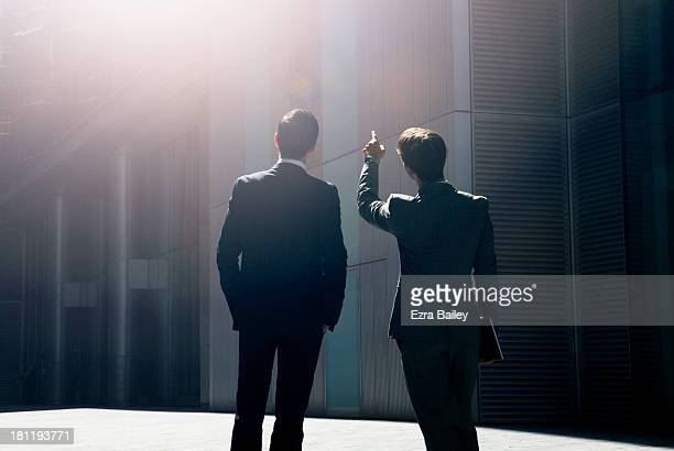 two businessmen looking up at city skyline. - double breasted stock pictures, royalty-free photos & images