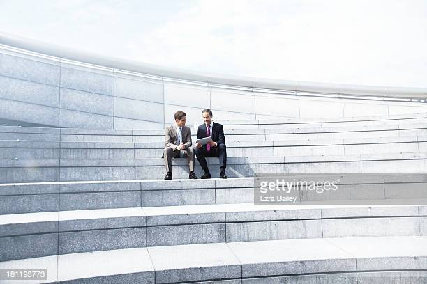 Two businessmen working in a tablet.