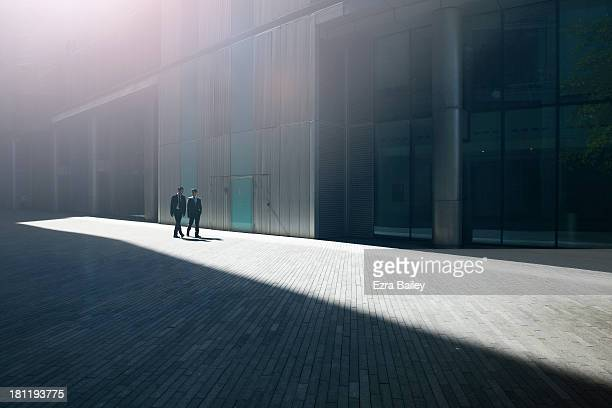 two businessmen walking through the city. - direction stock pictures, royalty-free photos & images
