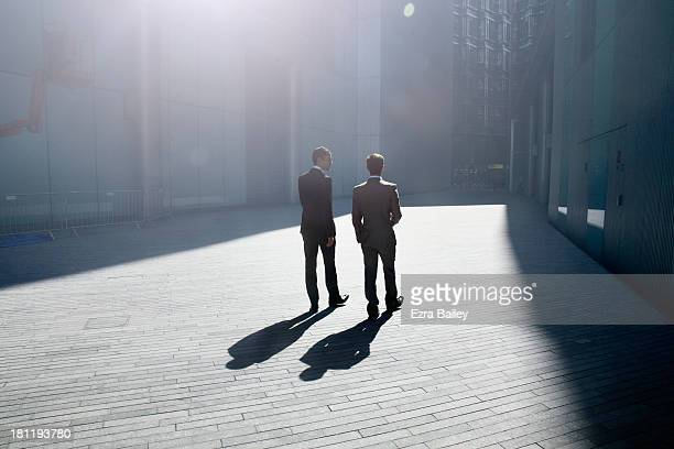 two businessmen walking through the city. - fianco a fianco foto e immagini stock