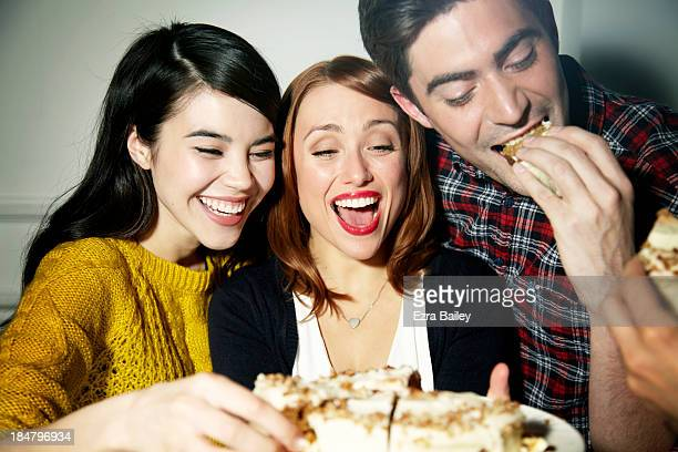 friends eating cake and laughing. - three people stock pictures, royalty-free photos & images