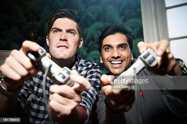friends in competition playing games console. - defeat stock pictures, royalty-free photos & images