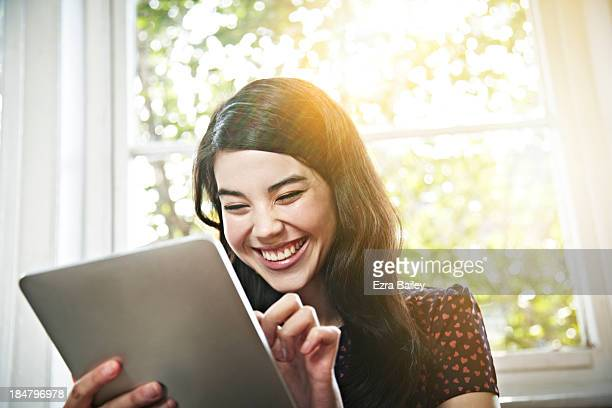 Mixed race woman using a tablet and smiling