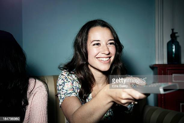 women with tv remote watching tv - ナイトイン ストックフォトと画像