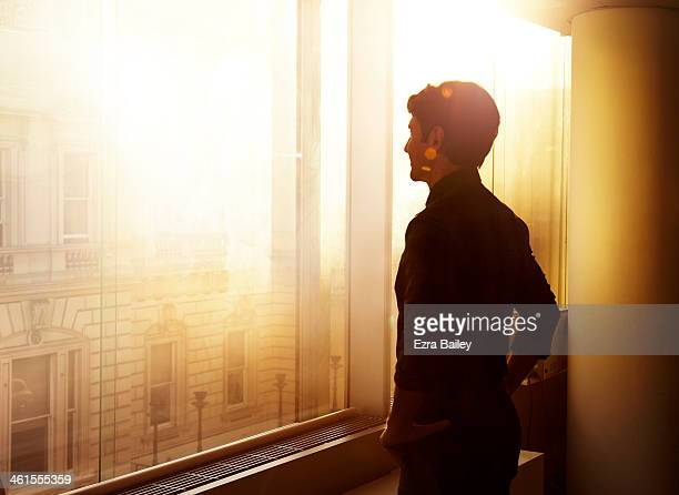 businessman looking out over the city at sunrise. - in silhouette stock pictures, royalty-free photos & images
