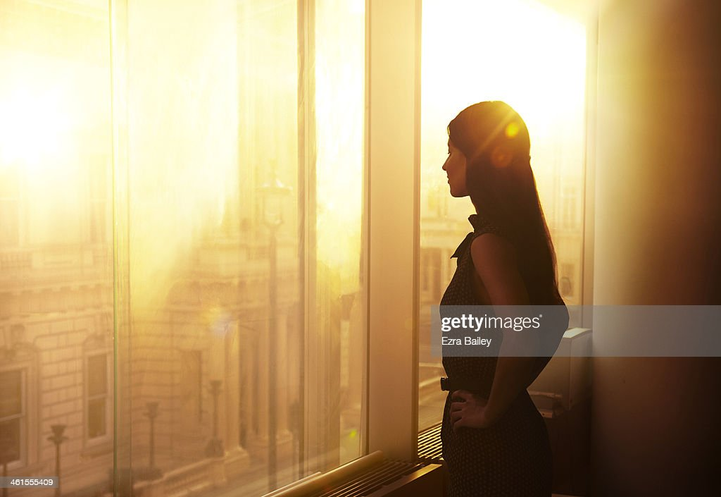 Business woman looking over the city at sunrise. : Stock Photo