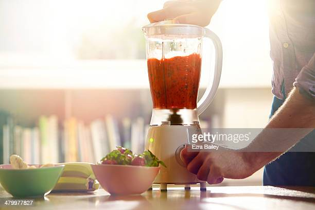 man making a smoothie at home. - juice drink stock photos and pictures