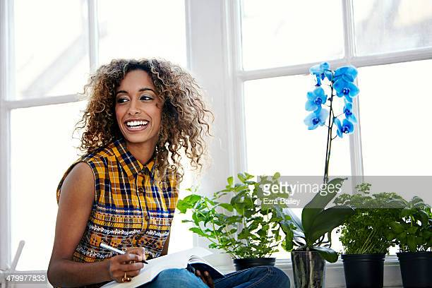 woman working surrounded by plants and flowers. - writer stock pictures, royalty-free photos & images