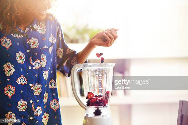 woman making a smoothie at home. - preparation stock pictures, royalty-free photos & images