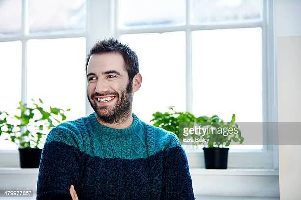 portrait of a man surrounded by plants. - jumper stock pictures, royalty-free photos & images