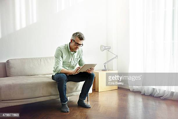 man using a tablet sitting in his apartment. - mature men stock pictures, royalty-free photos & images