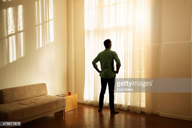 Man looking out of his apartment at sunrise.