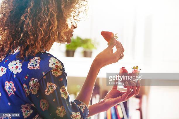 Woman eating strawberries at home.