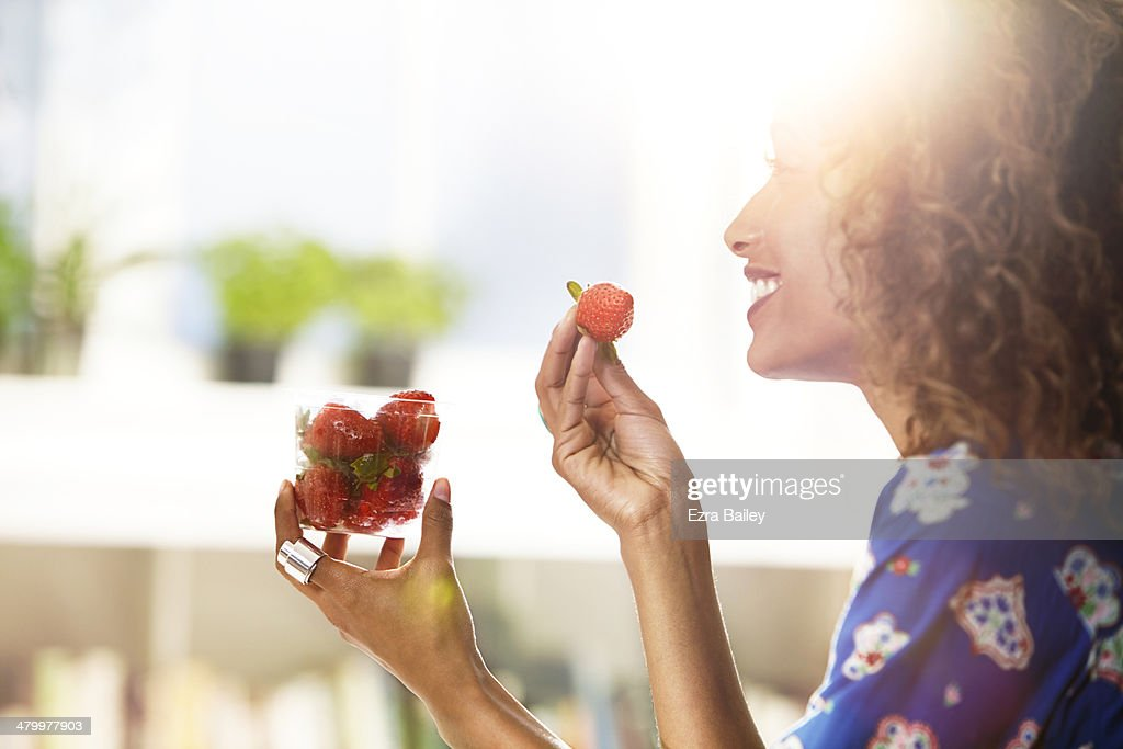 Woman eating strawberries at home. : ストックフォト