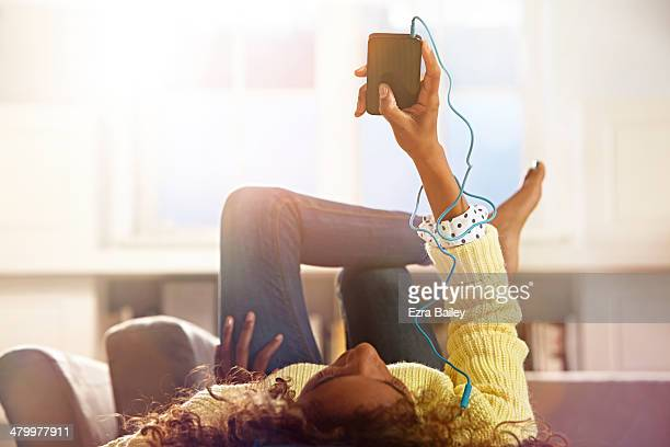 woman relaxing at home listening to her phone. - listening stock pictures, royalty-free photos & images