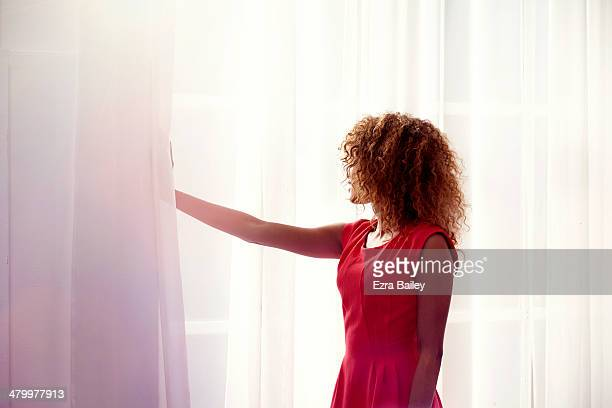 Mixed race woman looking through her window.